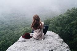 丘の上に座り込む女性
